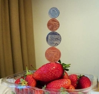 tower of 1p,2p,5p,10p UK coins balanced on a strawberry-Robin Linhope Willson