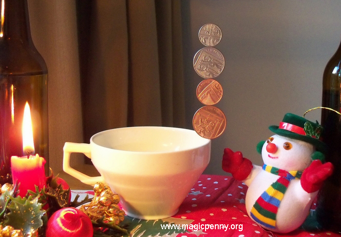 Four coins and  a teacup: a vertical column of  the 4 British magnetic coins balanced on the rim of a tea cup